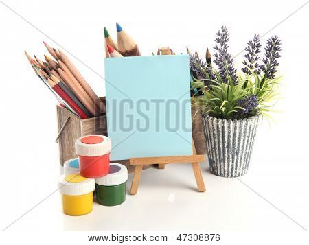 Different pencils in wooden crate, paints and easel, isolated on white