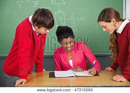 Young female teacher writing in binder while students standing at desk in classroom