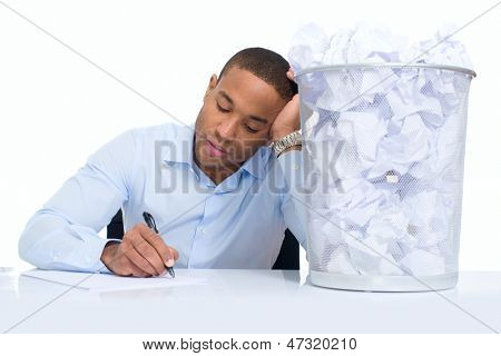 Businessman Sitting Besides Dustbin Over White Background