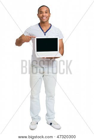 Young African Man Pointing Towards Laptop Over White Background
