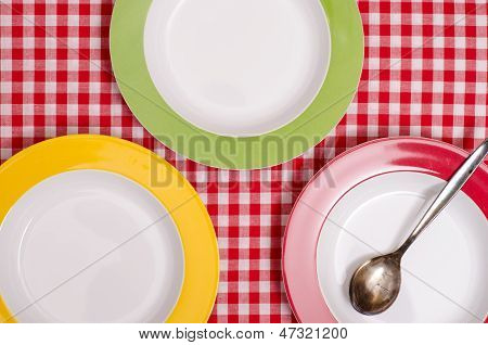 Three Coloured Plates And A Spoon