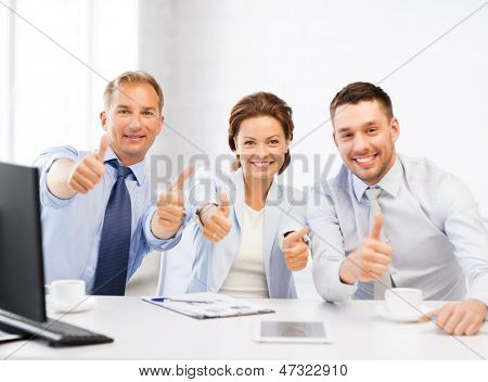 friendly business team showing thumbs up in office