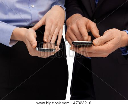 close up of woman and man hands with smartphones