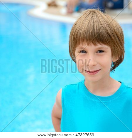 Summer portrait of carefree little boy outdoor near swimming-pool
