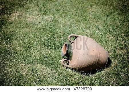 ancient jug are on grass-plot, toned