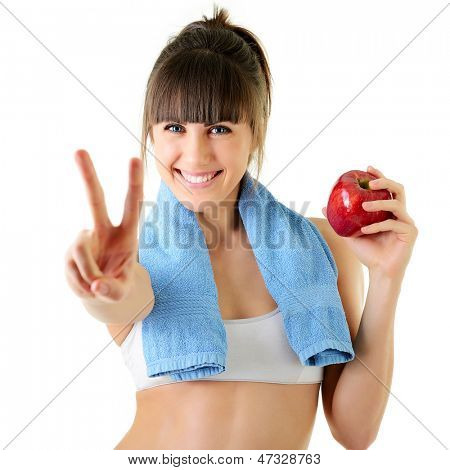 sport young woman with perfect body show victory gesture and holding an apple, fitness girl studio shot over white background