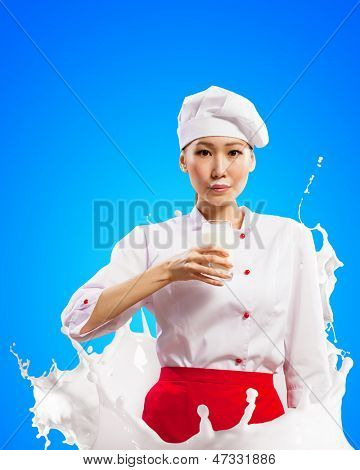 Asian female cook against milk splashes in red apron against color background holding glass of milk