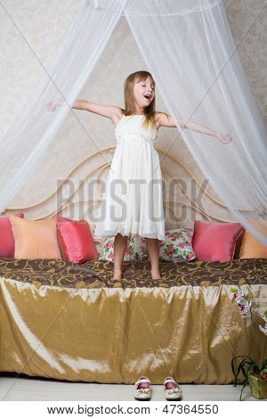 A little girl standing on the large bed and yawns