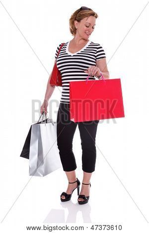 A well dressed mature woman holding shopping bags and checking the time on her watch, isolated on a white background.