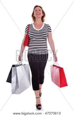 A smartly dressed woman in her early 40s carrying shopping bags, isolated on a white background.