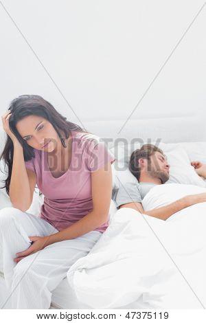 Betonte Frau denken, während sie in ihrem Bett neben ihrem Partner saß ist
