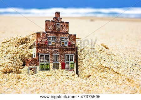 House disappearing in the sand. Concept for real estate in crisis time