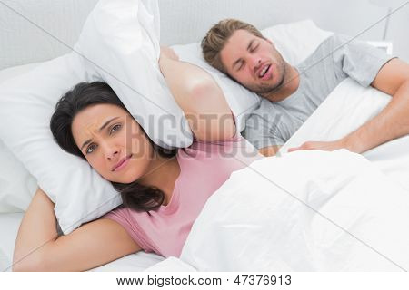 Woman covering ears with pillow while her husband is snoring next to her