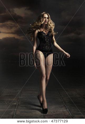 Gorgeous blondie over dark cloud background