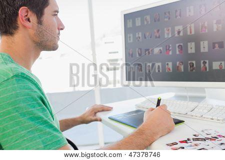 Concentrado photo editor trabajando en tableta gráfica en su escritorio