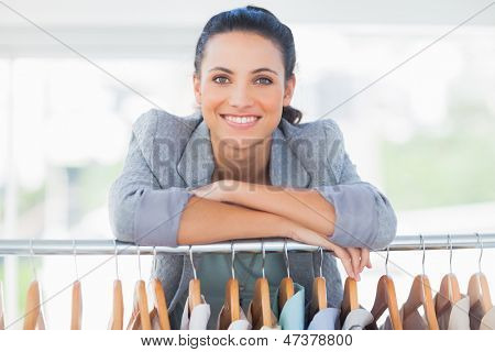 Attractive fashion designer leaning on clothes in a studio