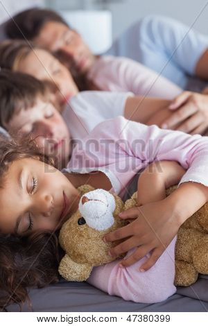Cute family napping together in bed
