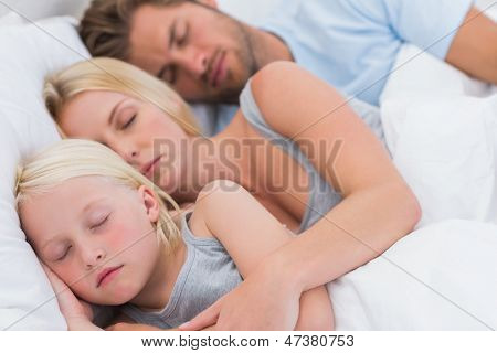 Cute couple sleeping with daughter in bed