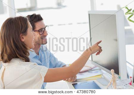 Editor de foto atractiva apuntando a la pantalla mientras trabajaba con una colega