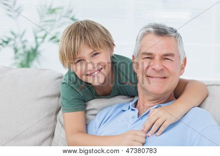 Portrait of grandson embracing grandfather sitting on the couch
