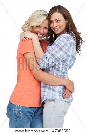 Two cute friends looking at the camera and hugging on white background