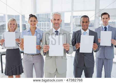 Buisness team holding up blank pages and smiling at camera