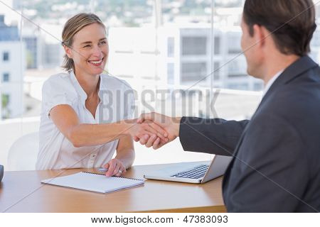 Cheerful interviewer shaking hand of an interviewee during a job interview