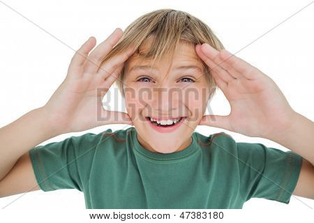 Surpised boy smiling with hands raised on white background