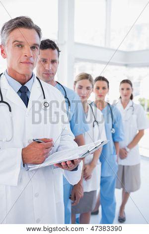 Doctor serio sosteniendo el portapapeles y parado frente a su equipo médico en fila