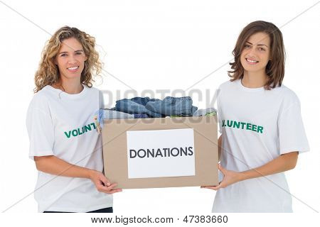 Two cheerful volunteers carrying clothes donation box on white background