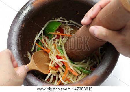 making of green papaya salad, som tam, thai food, ingredients are mixing and pounding in a mortar.