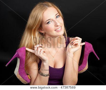 Porträt der schönen jungen blonden Frau mit Schuhen in Händen