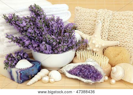 Lavender flowers with handmade soap, bath crystals, bathroom accessories and shells over bamboo background.