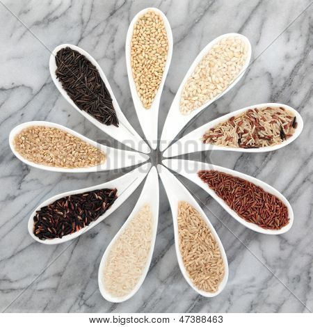 Rice grain selection in white porcelain bowls over marble background.