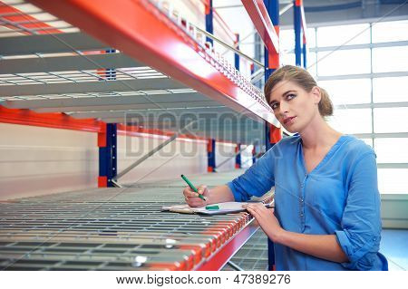 Female Worker Writing Inventory And Thinking In Warehouse