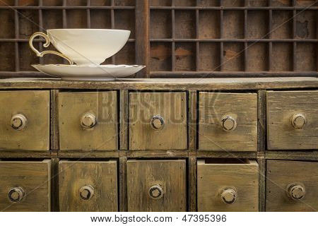 classic tea cup on top of rustic apothecary drawer cabinet