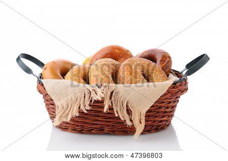 A basket of fresh baked bagels. Horizontal format isolated on white with reflection.