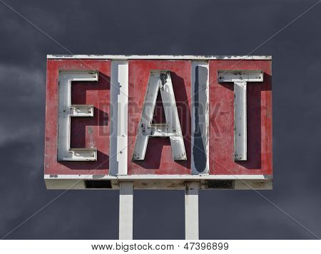 Vintage eat sign ruin with dark thunderstorm sky.