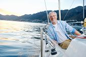 image of life-boat  - carefree happy sailing man portrait of mature retired man on ocean boat at sunrise - JPG