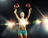 Young pretty boxer woman standing in light flashes