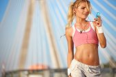 Stunning young blonde woman in pink sports bra rests and adjusting music on portable music player -