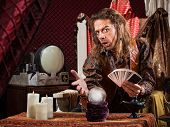 foto of enticing  - Enticing man with tarot cards and crystal ball - JPG