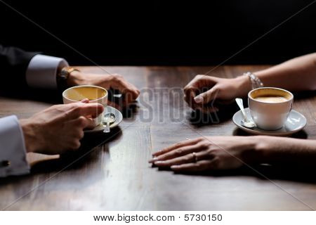 Bride's and groom's hands holding coffee cups