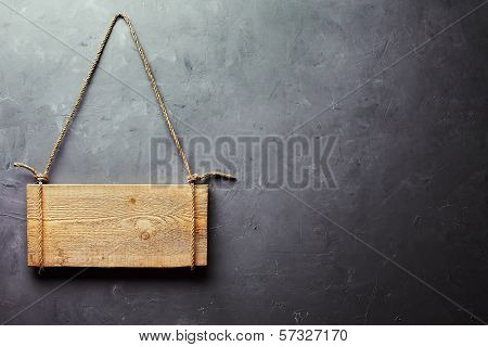 Wooden Signboard Hanging On Rope On Gray Textured Wall