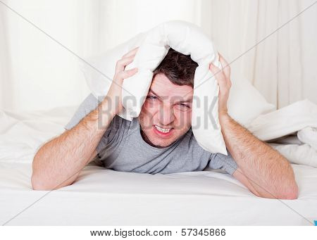 Man Suffering Hangover And Headache With Pillow On His Head