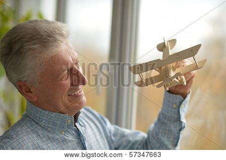 Senior man with wooden plane