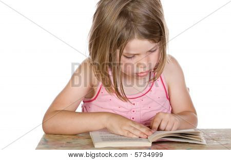 Shot Of A Cute Young Child Reading Her Book