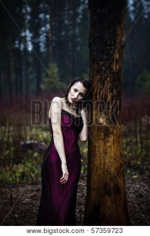 Pale woman in purple dress lying upon a tree