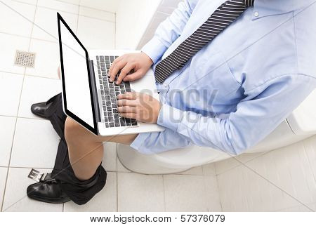 Businessman  Working  In Toilet With Laptop