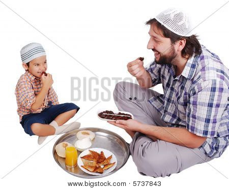 Young Muslim Man And His Son With Prepared Food For Iftar In Ramadan